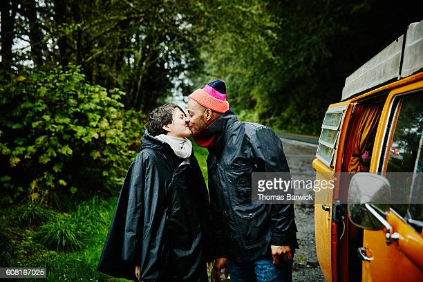 Couple on road trip standing next to van kissing