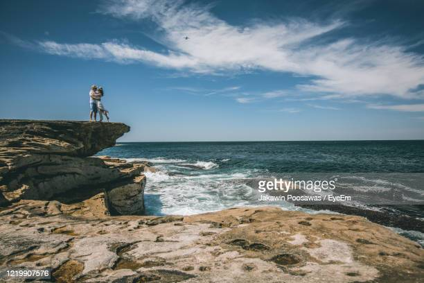 couple on rock by sea against sky - paris rocks stock pictures, royalty-free photos & images