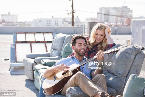 couple on rooptop sitting on sofa and playing guitar - heterosexual couple stock pictures, royalty-free photos & images