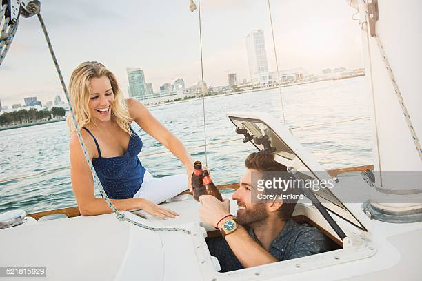 Couple on sailing boat with beer