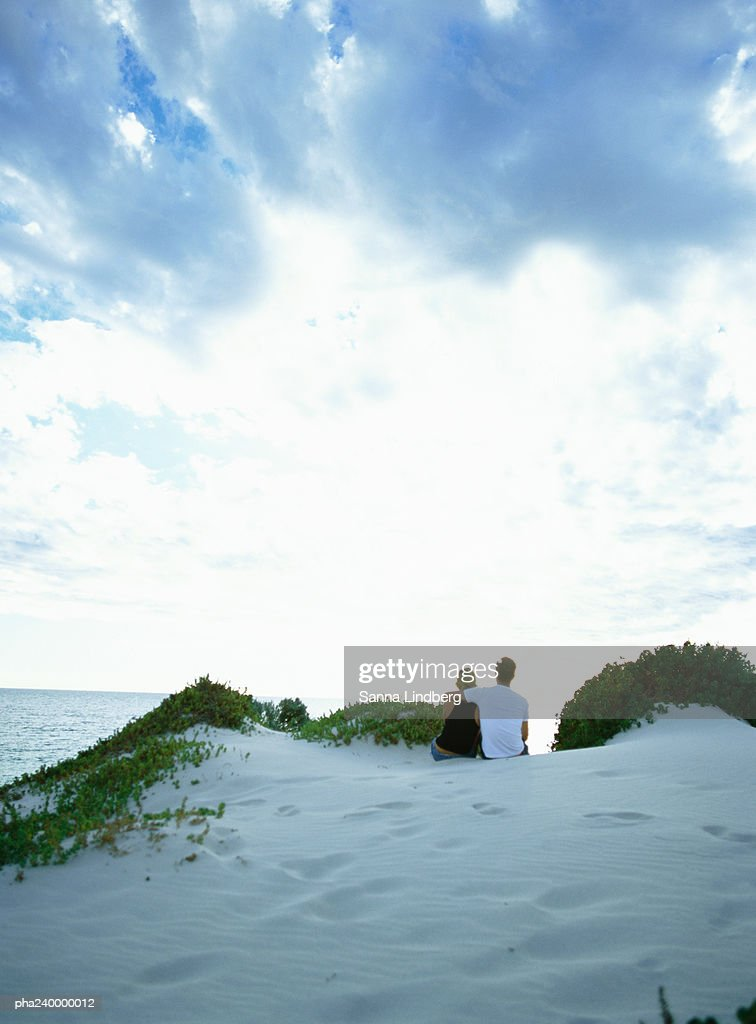 Couple on sand dune looking out to sea, rear view : Stockfoto