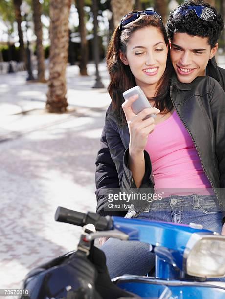 Paar auf Rollstuhl, die ein Handy