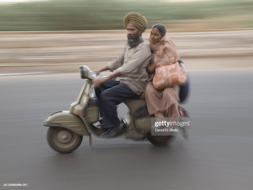 Couple on scooter (blurred motion) : Stockfoto