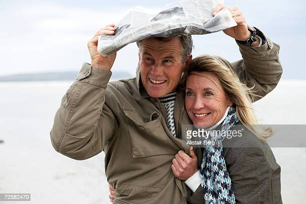 Couple on seashore, sheltering with newspaper
