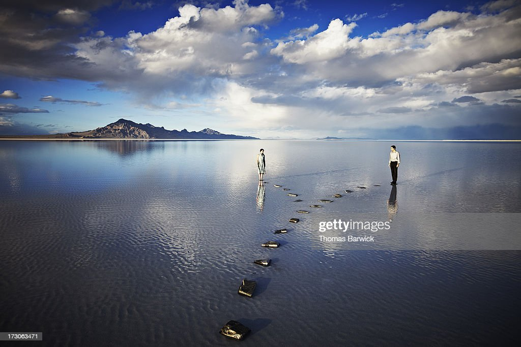 Couple on separate pathways in water : Stock Photo