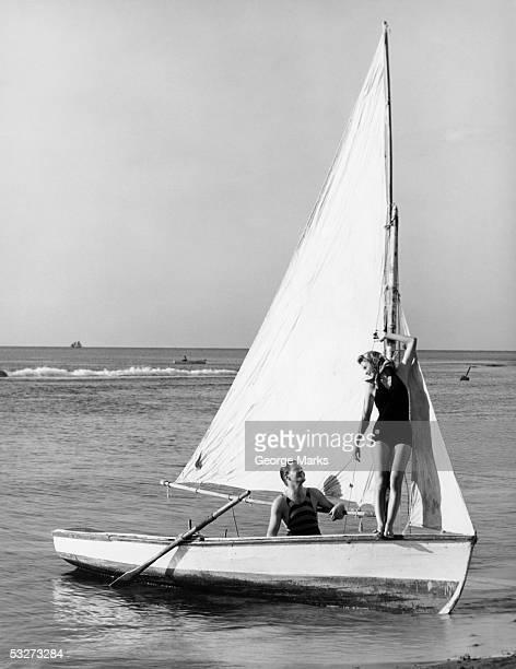 couple on small sail boat - voilier noir et blanc photos et images de collection