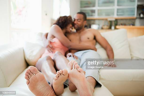 couple on sofa, focus on feet in foreground - male feet stock photos and pictures