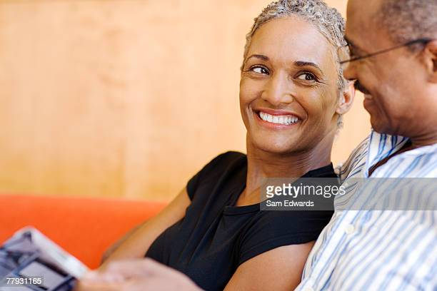 Couple on sofa in modern home with magazine