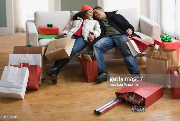 Couple on sofa surrounded by Christmas shopping bags