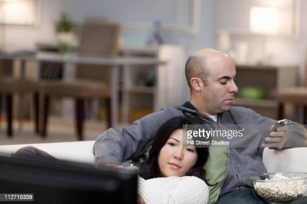 Couple sur le canapé ensemble regarder la télévision