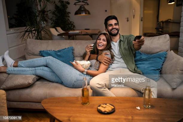 couple on sofa watching tv - girlfriends films stock pictures, royalty-free photos & images
