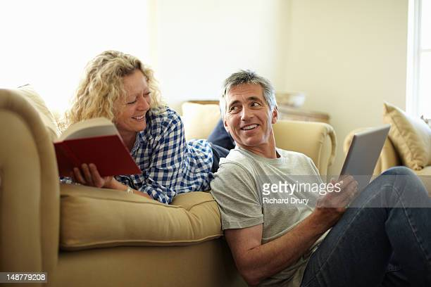 couple on sofa with book and digital tablet - heteroseksueel koppel stockfoto's en -beelden