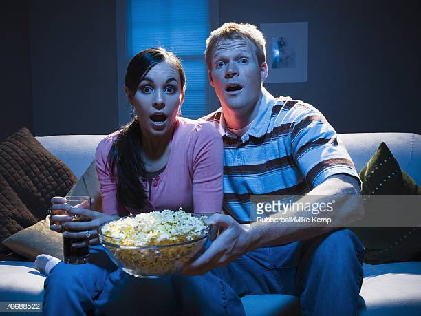 Couple on sofa with bowl of popcorn looking shocked