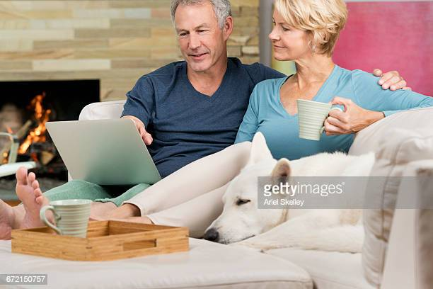 Couple on sofa with dog video using laptop