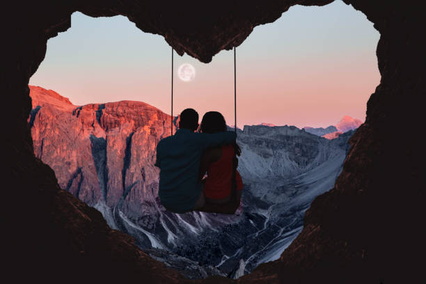 couple on swing contemplating the mountains in a romantic view with heart shape. - couples romance stock pictures, royalty-free photos & images