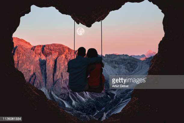 couple on swing contemplating the mountains in a romantic view with heart shape. - valentine's day holiday stock pictures, royalty-free photos & images