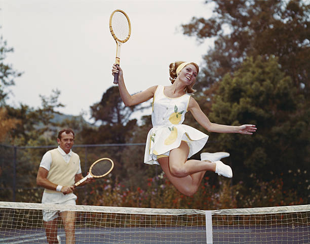Couple on tennis court, woman jumping in foreground