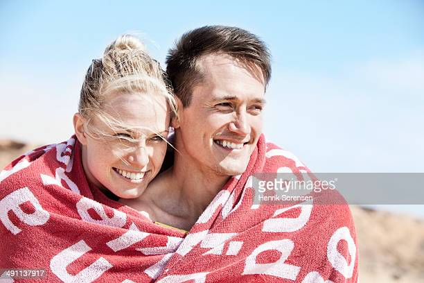 couple on the beach - wrapped in a towel stock pictures, royalty-free photos & images