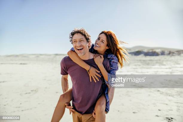 couple on the beach - candid beach stock photos and pictures