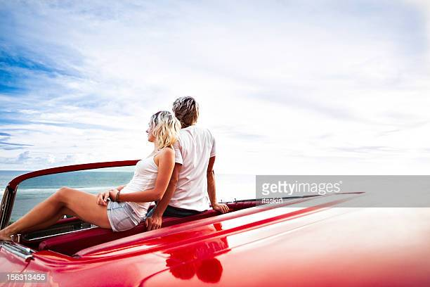 Couple on the cliff sitting in car