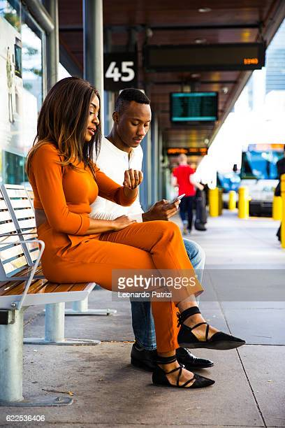 Couple on the move waiting for the bus