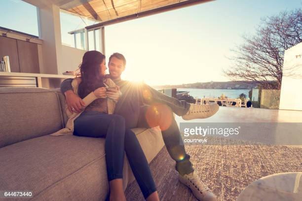 couple on the sofa at sunrise. - wealth stock pictures, royalty-free photos & images