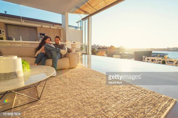 couple on the sofa at sunrise. they both have a cup of coffee. - wide angle stock pictures, royalty-free photos & images