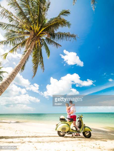 Couple on the sunny tropical beach with a green retro bike