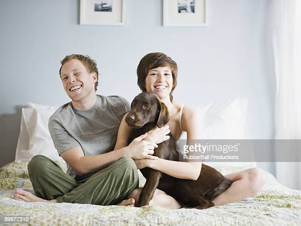 Paar auf Ihrem Bett mit Ihrem Hund