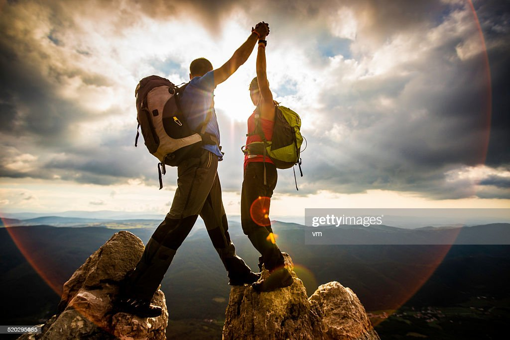 Couple on Top of a Mountain Shaking Raised Hands : Stock Photo
