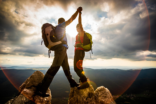 Couple on Top of a Mountain Shaking Raised Hands 520295685