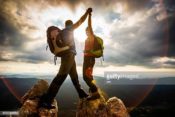 couple on top of a mountain shaking raised hands - motivatie stockfoto's en -beelden
