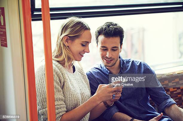 Couple on train using smart phone