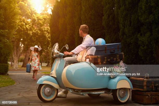 Couple on vacation with vintage scooter
