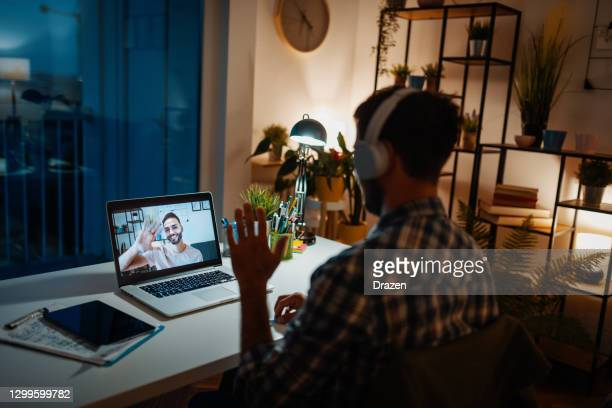 lgbt couple on video call during covid-19 lockdown. separated gay couple talking over video link - place of work stock pictures, royalty-free photos & images