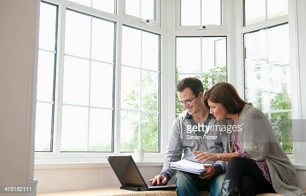 couple on window seat, using laptop - erker stockfoto's en -beelden