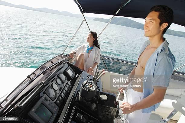 Couple on yacht, man steering, woman sitting, looking away