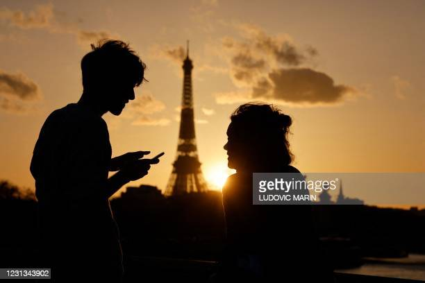 Couple, one checking his smartphone, enjoy the view of the Eiffel Tower at sunset in Paris on February 23, 2021.