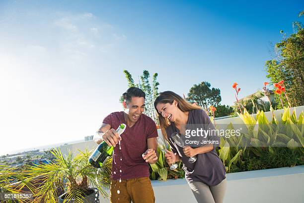 Couple opening champagne in penthouse rooftop garden, La Jolla, California, USA