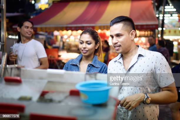 Couple ordering drinks from a street vendor at a night market