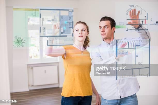 Couple organizing virtual house model