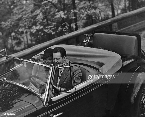 A couple out for a drive in a convertible with a set of golf clubs in the back seat circa 1940's