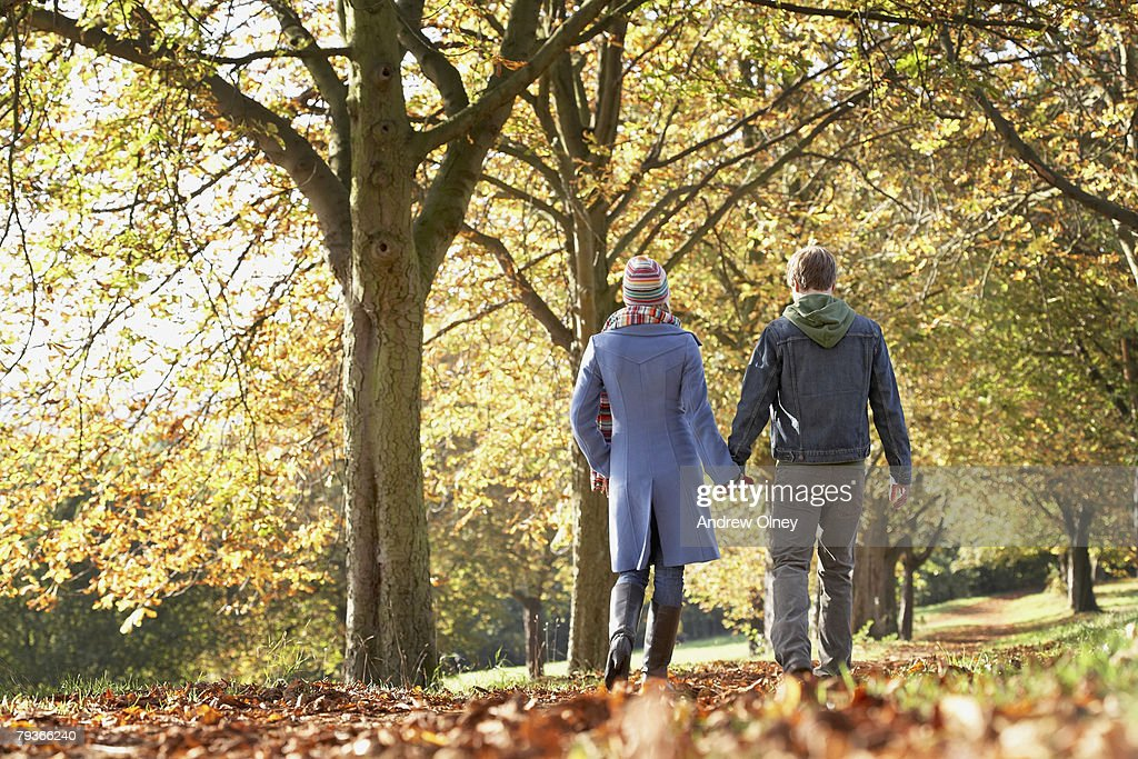 Couple outdoors at a park holding hands : Stockfoto