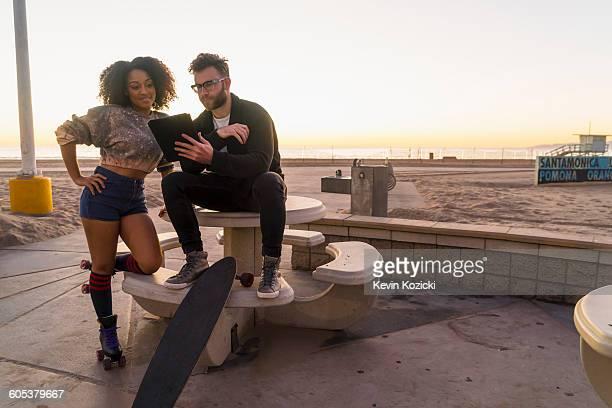 Couple outdoors, beside beach, looking at digital tablet, woman wearing rollerskates