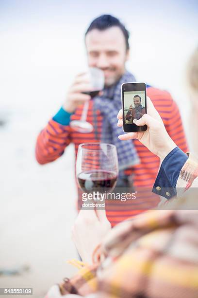 Couple outdoors, drinking wine, woman taking photograph of man