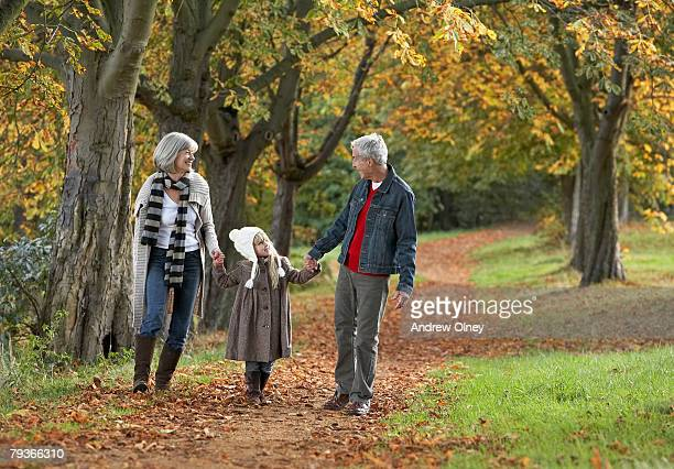 Couple outdoors holding hands with a young girl in a park