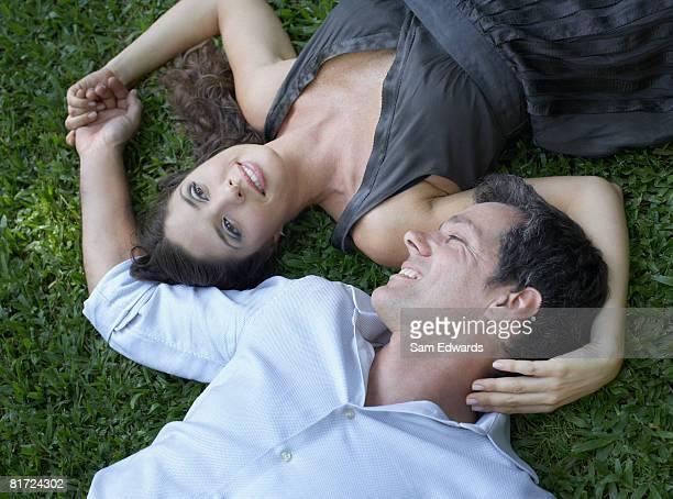 Casal deitado na grama juntos ao ar livre de mãos dadas e smilin