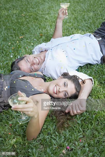 Casal deitado na grama ao ar livre com vinho branco e