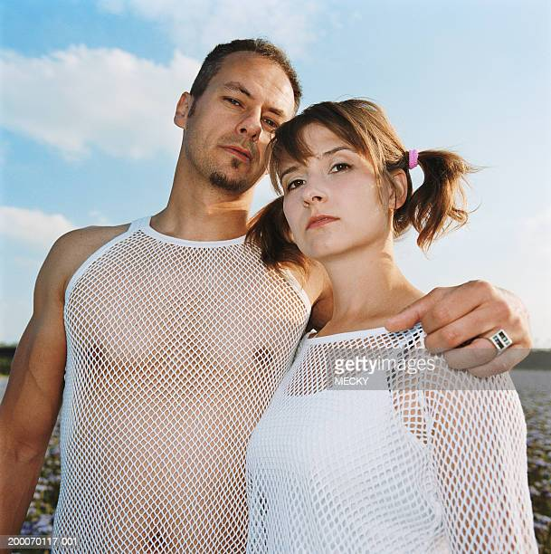 couple outdoors, man with arm around woman's shoulder, portrait - mesh shirt stock photos and pictures