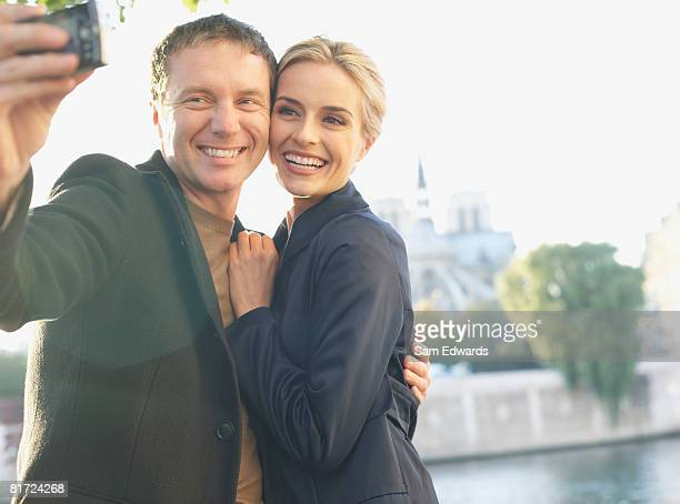 couple outdoors taking self-portrait using digital camera smiling - may december romance stock photos and pictures